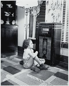 Young girl sitting on floor in front of an electric radio in the 1940s